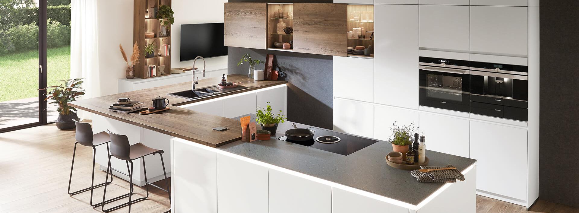 weiße grifflose Küche mit Tisch und Holz-Optik matte Front mit LED Beleuchtung