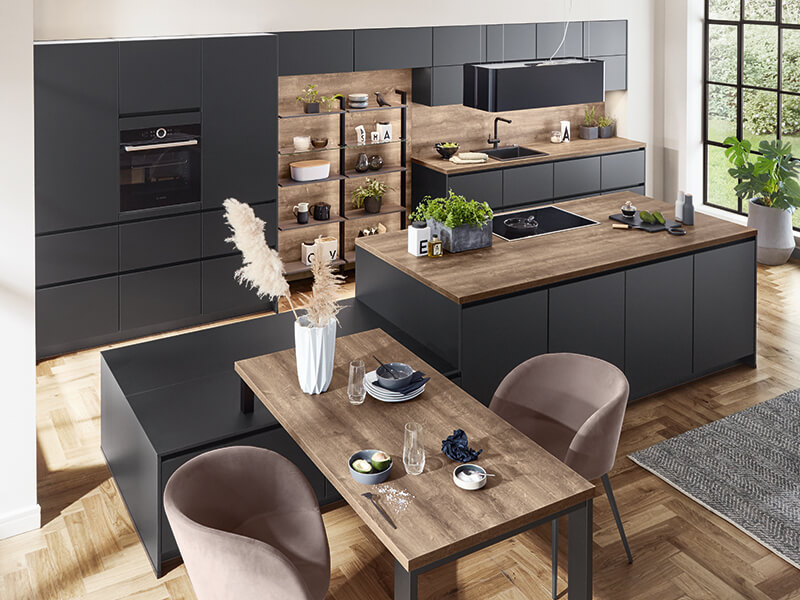 moderne große Kücheninsel und Küchenzeile in dunkel grau schwarz und Holz-Optik mit Elektrogeräte